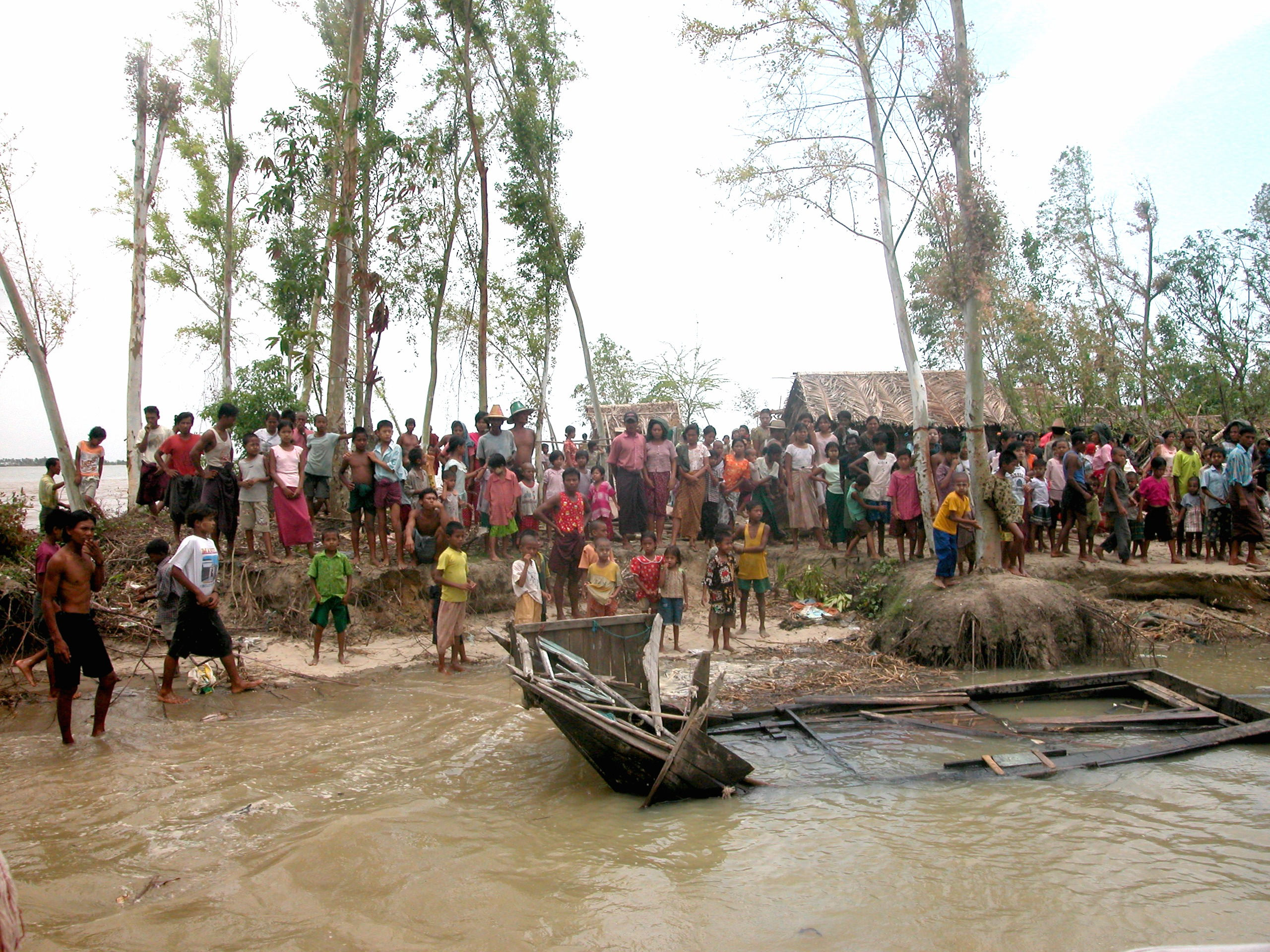 A group of villagers look at a damaged house