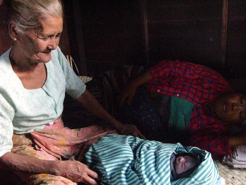 An older Burmese woman looks at a newborn baby