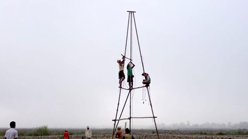 A group of people build a well in a field in Burma