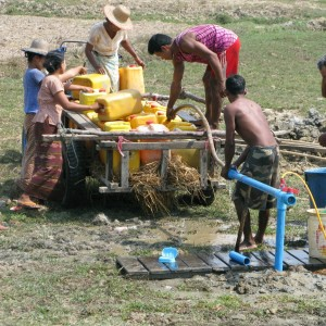 A group of men building a water well in Burma